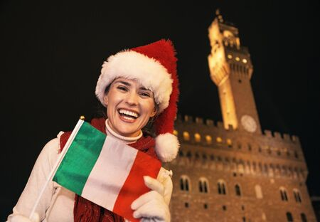 Trip full of inspiration at Christmas time in Florence. Portrait of smiling modern tourist woman in Christmas hat in the front of Palazzo Vecchio in Florence, Italy with Italian flag