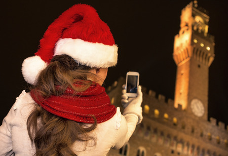 Trip full of inspiration at Christmas time in Florence. Modern tourist woman in Christmas hat in the front of Palazzo Vecchio in Florence, Italy taking photo  with cellphone Stock Photo