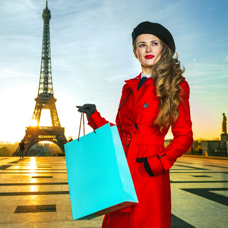 Bright in Paris. young tourist woman in red coat in the front of Eiffel tower in Paris, France with shopping bag looking into the distance 版權商用圖片