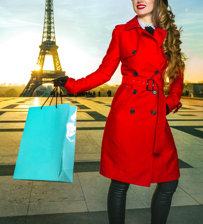 Bright in Paris. smiling elegant tourist woman in red coat in the front of Eiffel tower in Paris, France holding shopping bag