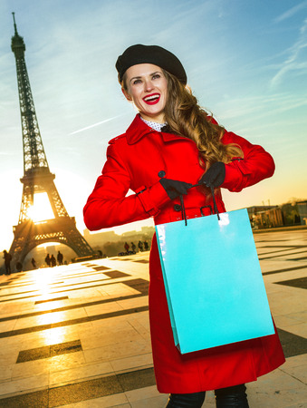 Bright in Paris. smiling elegant woman in red coat in the front of Eiffel tower in Paris, France holding shopping bag