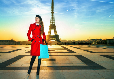 Bright in Paris. Full length portrait of modern tourist woman in red coat against Eiffel tower in Paris, France with shopping bag looking into the distance Reklamní fotografie