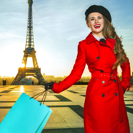 Bright in Paris. happy modern woman in red coat in Paris, France with shopping bag looking into the distance 版權商用圖片