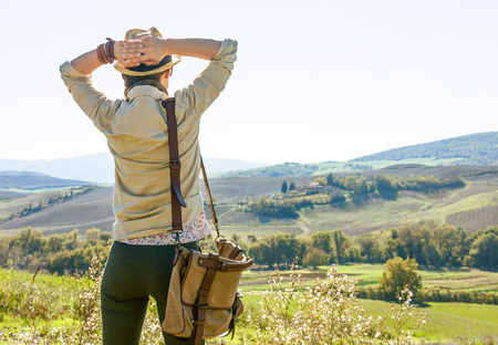 relaxed adventure woman hiker in hat with bag hiking in Tuscany