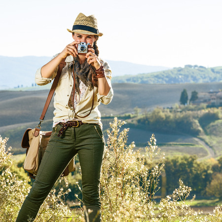 Discovering magical views of Tuscany. healthy woman hiker with bag hiking in Tuscany taking photo with vintage photo camera