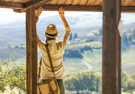 Discovering magical views of Tuscany. Seen from behind woman hiker in hat in Tuscany looking into the distance and enjoying scenery while Stock Photo