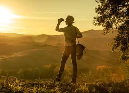 Discovering magical views of Tuscany. Full length portrait of adventure woman hiker with bag enjoying sunset in Tuscany while looking into the distance through binoculars