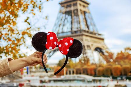 디즈니 랜드와 파리의 완벽한 가을 휴가. 미니 마우스 근접 촬영 프랑스 파리에서에서 에펠 탑 근처 제방에 여성의 손에 귀 스톡 콘텐츠