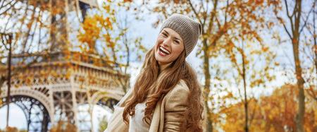 Autumn getaways in Paris. Portrait of happy young woman near Eiffel tower having fun time