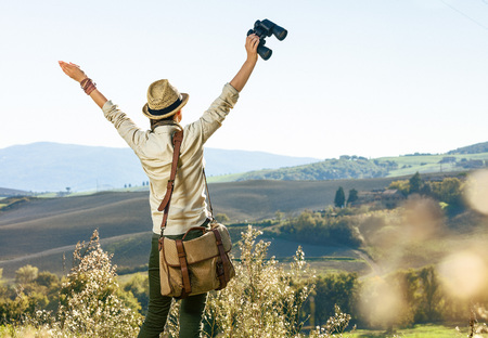 Discovering magical views of Tuscany. Seen from behind woman hiker with bag hiking in Tuscany with binoculars rejoicing