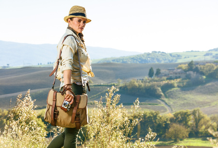 Discovering magical views of Tuscany. Portrait of active woman hiker with bag enjoying Tuscany view with vintage photo camera