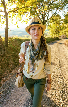 Discovering magical views of Tuscany. active woman hiker with bag on Tuscany hike