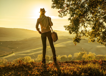 Discovering magical views of Tuscany. Seen from behind active woman hiker in hat with bag enjoying sunset in Tuscany
