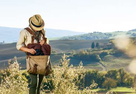 Discovering magical views of Tuscany. young woman hiker with bag hiking in Tuscany taking binoculars
