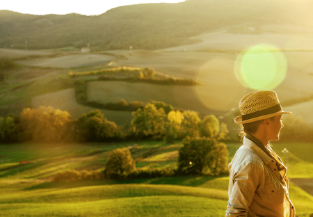 Discovering magical views of Tuscany. woman hiker in hat enjoying evening in Tuscany and looking into the distance