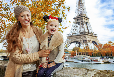 Perfect autumn holidays in Disneyland and Paris. Portrait of smiling tourists mother and daughter in Minnie Mouse Ears on embankment near Eiffel tower in Paris, France sitting on the parapet