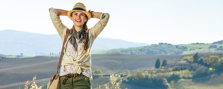 Discovering magical views of Tuscany. relaxed woman hiker in hat with bag enjoying Tuscany view looking into the distance