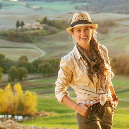 Discovering magical views of Tuscany. Portrait of adventure woman hiker in hat enjoying evening in Tuscany Stock Photo