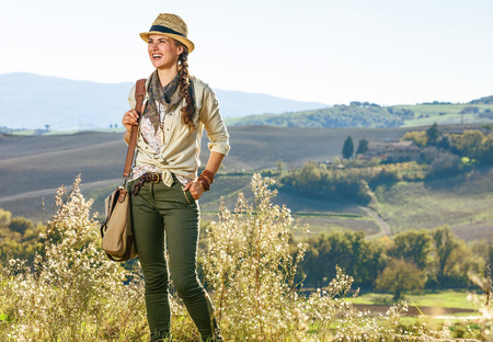 Discovering magical views of Tuscany. happy active woman hiker with bag enjoying Tuscany view looking into the distance Stock Photo