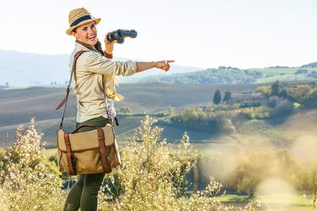 Discovering magical views of Tuscany. happy healthy woman hiker in hat hiking in Tuscany with binoculars pointing at something