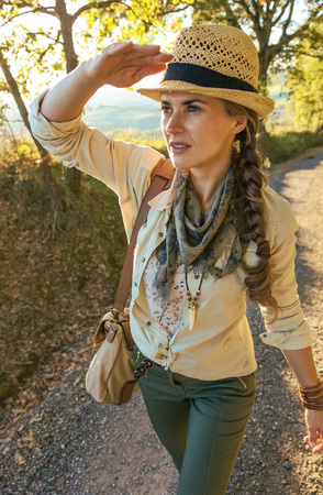 Discovering magical views of Tuscany. adventure woman hiker with bag hiking in Tuscany and looking into the distance Stock Photo
