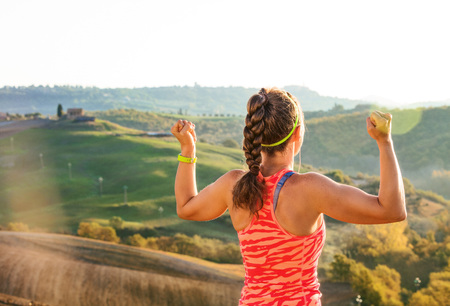 Fitness and magical views of Tuscany. Seen from behind fit woman jogger in sport clothes in the front of scenery of Tuscany rejoicing