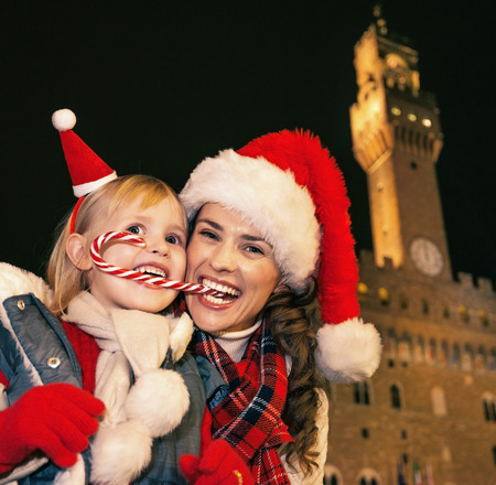 Trip full of inspiration at Christmas time in Florence. Portrait of happy young mother and child travellers in Christmas hats against Palazzo Vecchio in Florence, Italy eating Christmas candy cane