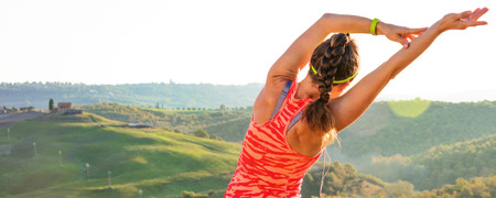 Fitness and magical views of Tuscany. Seen from behind young fit woman in sports gear against scenery of Tuscany stretching