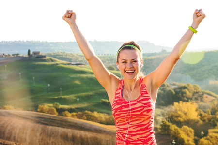 Fitness and magical views of Tuscany. Portrait of smiling active active woman in sports gear against scenery of Tuscany rejoicing