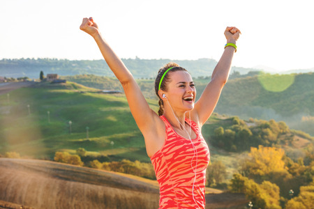 Fitness and magical views of Tuscany. Portrait of smiling sportswoman in sports gear against scenery of Tuscany rejoicing