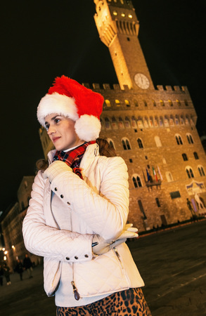 Trip full of inspiration at Christmas time in Florence. pensive young woman in Christmas hat in Florence, Italy looking into the distance