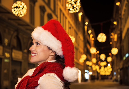 Trip full of inspiration at Christmas time in Florence. Portrait of happy modern woman in Christmas hat at Christmas in Florence, Italy