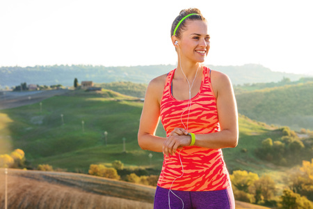 Fitness and magical views of Tuscany. happy healthy fit woman in sport clothes against scenery of Tuscany looking into the distance and using activity tracker