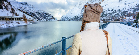 Winter on higher level of fun. Seen from behind stylish woman against mountain scenery with lake in Alto Adige, Italy Stock Photo