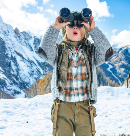 Winter on higher level of fun. modern mother and child travellers in the front of mountain scenery in Alto Adige, Italy looking into the distance through binoculars