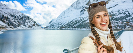 Winter on higher level of fun. Portrait of smiling modern traveller woman in the front of mountain landscape with lake in Alto Adige, Italy
