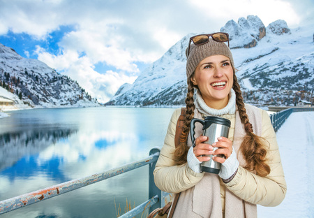 Winter on higher level of fun. happy elegant tourist woman in the front of mountain landscape with lake in Alto Adige, Italy with thermos travel mug looking into the distance