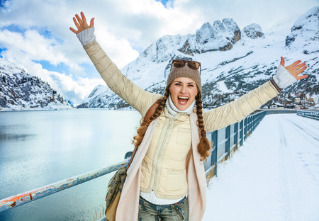Winter on higher level of fun. Portrait of happy stylish traveller woman in the front of mountain landscape with lake in Alto Adige, Italy rejoicing 版權商用圖片