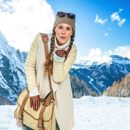 Winter on higher level of fun. Portrait of happy elegant traveller woman in the front of mountain scenery in Alto Adige, Italy blowing air kiss
