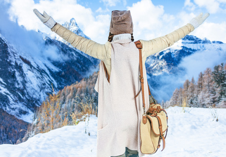 Winter on higher level of fun. Seen from behind modern traveller woman in the front of mountain scenery in South Tyrol, Italy rejoicing