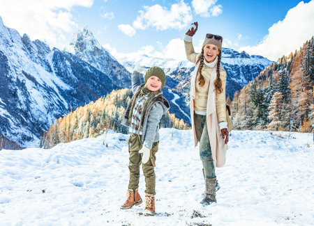 Winter on higher level of fun. Full length portrait of modern mother and daughter travellers in the front of mountain landscape in Alto Adige, Italy playing snowballs