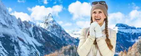 Winter on higher level of fun. Portrait of smiling modern traveller woman in the front of mountain scenery in South Tyrol, Italy warming hands with breath