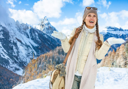 Winter on higher level of fun. smiling modern traveller woman in the front of mountain landscape in Alto Adige, Italy catching snowflakes 版權商用圖片