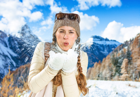 Winter on higher level of fun. smiling modern traveller woman in the front of mountain scenery in Alto Adige, Italy blowing snow at camera Stock fotó
