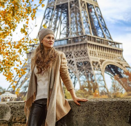 Autumn getaways in Paris. pensive young tourist woman on embankment near Eiffel tower in Paris, France looking into the distance