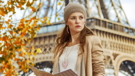 Autumn getaways in Paris. young elegant woman on embankment in Paris, France with map looking into the distance