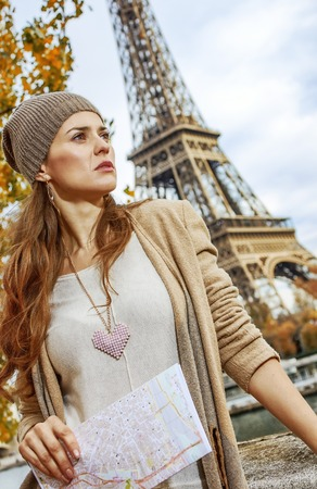 Autumn getaways in Paris. young tourist woman on embankment in Paris, France with map looking into the distance