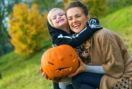 Trick or Treat. smiling modern mother and daughter on Halloween outdoors with pumpkin Jack O Lantern