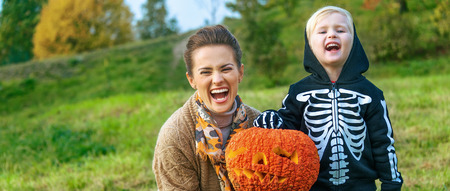 Trick or Treat. smiling modern mother and child on Halloween at the park showing pumpkin Jack O'Lantern