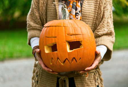 Trick or Treat. Closeup on modern woman on Halloween at the park showing carved pumpkin